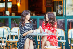 Beautiful twin sisters drinking coffee Stock Photos
