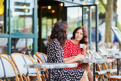 Beautiful twin sisters drinking coffee Stock Images