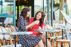 Beautiful twin sisters drinking coffee in Paris Royalty Free Stock Photography