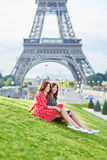 Beautiful twin sisters in front of the Eiffel tower in Paris, France Stock Photo