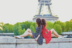 Beautiful twin sisters in front of the Eiffel tower in Paris Stock Photography