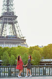 Beautiful twin sisters in front of the Eiffel tower in Paris Royalty Free Stock Photography
