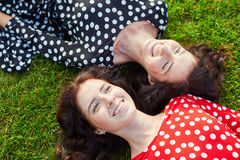 Beautiful twin sisters lying on the grass Royalty Free Stock Photography