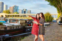 Beautiful twin sisters near the river Seine in Paris, France Royalty Free Stock Photography