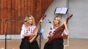 Beautiful twin sisters playing banduras - Ukrainian string instrument Stock Photo