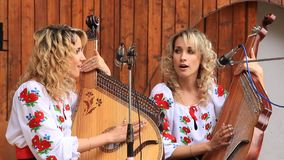 Beautiful twin sisters playing banduras - Ukrainian string instrument Royalty Free Stock Photo