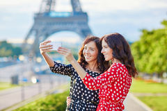 Beautiful twin sisters taking selfie in front of Eiffel Tower Stock Images