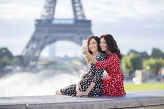 Beautiful twin sisters taking selfie in front of Eiffel Tower Royalty Free Stock Photo