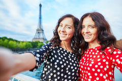 Beautiful twin sisters taking selfie in front of Eiffel Tower Royalty Free Stock Photos