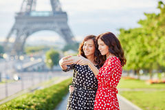 Beautiful twin sisters taking selfie in front of Eiffel Tower Royalty Free Stock Photography