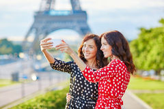 Beautiful twin sisters taking selfie in front of Eiffel Tower Royalty Free Stock Image