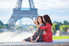 Beautiful twin sisters taking selfie in front of Eiffel Tower Stock Photos