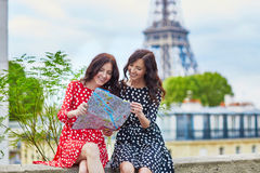 Beautiful twin sisters using map in front of Eiffel Tower. While traveling in Paris, France. Happy smiling girls enjoy their vacation in Europe Stock Photos