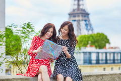 Beautiful twin sisters using map in front of Eiffel Tower. While traveling in Paris, France. Happy smiling girls enjoy their vacation in Europe Royalty Free Stock Photo