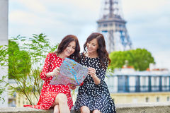 Beautiful twin sisters using map in Paris. Beautiful twin sisters using map in front of Eiffel Tower while traveling in Paris, France. Happy smiling girls enjoy Stock Photo