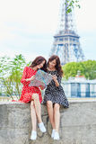 Beautiful twin sisters using map in Paris. Beautiful twin sisters using map in front of Eiffel Tower while traveling in Paris, France. Happy smiling girls enjoy Royalty Free Stock Photography