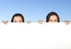 Beautiful twins holding a white board Royalty Free Stock Photo