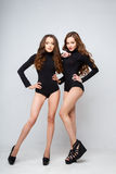 Beautiful twins young women in black bodies over white background. Stock Photography