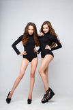 Beautiful twins young women in black bodies over white background. Stock Image
