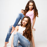 Beautiful twins young women in casual clothes over white background. Beauty fashion portrait Stock Image