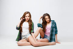 Beautiful twins young women in casual clothes over white background. Beauty fashion portrait Royalty Free Stock Photos
