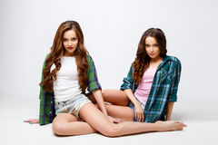 Beautiful twins young women in casual clothes over white background. Beauty fashion portrait Stock Photo