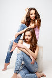Beautiful twins young women in casual clothes over white background. Beauty fashion portrait Royalty Free Stock Photography