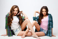 Beautiful twins young women in casual clothes over white background. Beauty fashion portrait Stock Photography