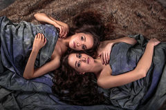Beautiful twins young women with natural make-up and hair style lying with their curly hair surround them Stock Photography
