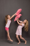 Beautiful two girls in pink pajamas play before going to bed. Sisters in pajamas are getting ready for bed. Fighting with pillows before bedtime Royalty Free Stock Image