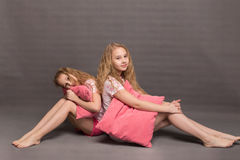 Beautiful two girls in pink pajamas play before going to bed. Sisters in pajamas are getting ready for bed. Fighting with pillows before bedtime Royalty Free Stock Photos