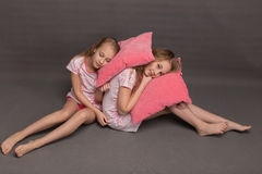Beautiful two girls in pink pajamas play before going to bed. Sisters in pajamas are getting ready for bed. Fighting with pillows before bedtime Royalty Free Stock Images