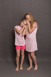 Beautiful two girls in pink pajamas play before going to bed. Sisters in pajamas are getting ready for bed. Fighting with pillows before bedtime Stock Images