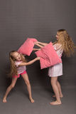 Beautiful two girls in pink pajamas play before going to bed. Sisters in pajamas are getting ready for bed. Fighting with pillows before bedtime Royalty Free Stock Photography