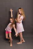 Beautiful two girls in pink pajamas play before going to bed. Sisters in pajamas are getting ready for bed. Fighting with pillows before bedtime Stock Photo