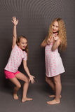 Beautiful two girls in pink pajamas play before going to bed Stock Photo