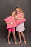 Beautiful two girls in pink pajamas play before going to bed Stock Image