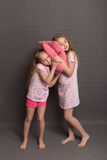 Beautiful two girls in pink pajamas play before going to bed Royalty Free Stock Images