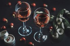 Rose wine and Christmas ornaments on wooden table on black wooden table royalty free stock image