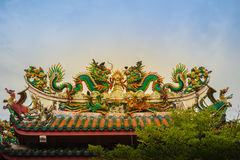 Beautiful two large grimace dragons crawling on decorative tiles. Roof in Chinese temple. Colorful roof detail of traditional Chinese temple with two dragon on Royalty Free Stock Images