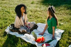 Beautiful two multi-race female friends are happily talking on a picnic in the park. Royalty Free Stock Images
