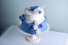 Beautiful two tiered white and blue wedding cake decorated with flowers sugar roses. Concept of elegant holiday desserts. Beautiful two tiered white and blue Stock Photos