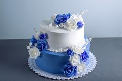 Beautiful two tiered white and blue wedding cake decorated with flowers sugar roses. Concept of elegant holiday desserts. Beautiful two tiered white and blue Royalty Free Stock Photography