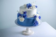 Beautiful two tiered white and blue wedding cake decorated with flowers sugar roses. Concept of elegant holiday desserts. Beautiful two tiered white and blue Stock Images