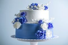 Beautiful two tiered white and blue wedding cake decorated with flowers sugar roses. Concept of elegant holiday desserts. Beautiful two tiered white and blue Stock Photography