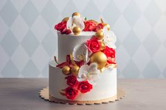 Beautiful two-tiered white wedding cake decorated with red roses. Concept of elegant holiday desserts Stock Photography