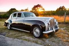 Luxurious, two-toned, vintage limousine on a rural Texas road at sunset. Beautiful, two-toned, vintage luxury limousine with sweeping fenders, chrome bumpers Stock Images