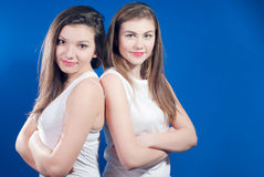 Beautiful two young woman standing back to back Royalty Free Stock Photography