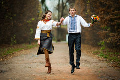 Beautiful ukrainian bride and groom jumping in native embroidery stock photography