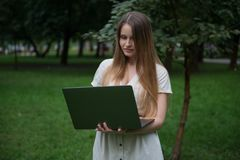 Beautiful ukrainian girl in beige dress staying in park with laptop. She is free without office routine. Royalty Free Stock Image